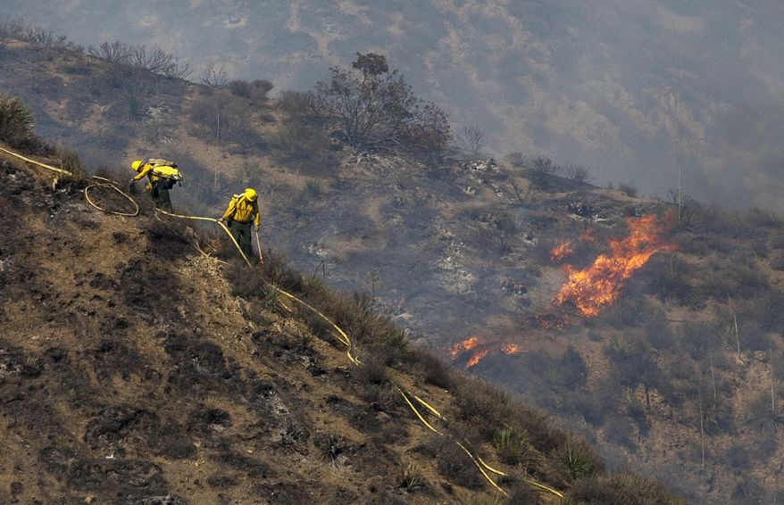 Firefighters work at a burned area on a hillside during a wildfire in Camarillo, Calif., Thursday, May 2, 2013. (AP Photo/Ringo H.W. Chiu)
