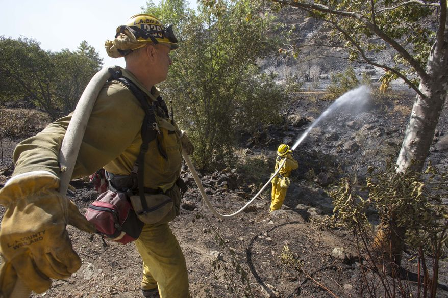Firefighters douse a burned area along the hillside near the student dorm of  Cal State, Channel Islands in Camarillo, Calif., Thursday, May 2, 2013. (AP Photo/Ringo H.W. Chiu)