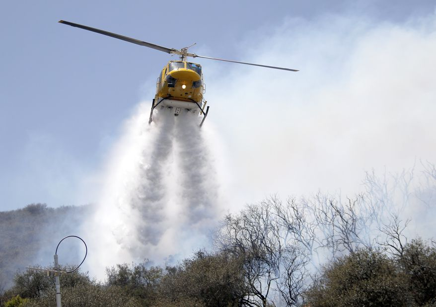 A helicopter drops water on a hotspot over a hill near Thousand Oaks, Calif. on Thursday, May 2, 2013. A wildfire fanned by gusty Santa Ana winds raged along the fringes of Southern California communities on Thursday, forcing evacuation of homes and a university while setting recreational vehicles ablaze. (AP Photo/Nick Ut)