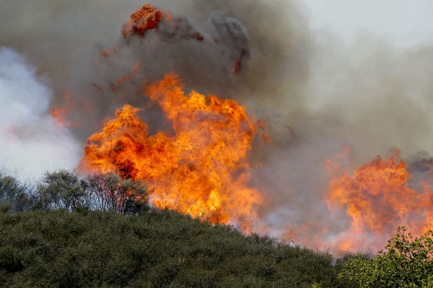 Smoke and fire billows over a hill near Thousand Oaks, Calif. on Thursday, May 2, 2013. Authorities have ordered evacuations of a neighborhood and a university about 50 miles west of Los Angeles where a wildfire is raging close to subdivisions.  (AP Photo/Nick Ut)