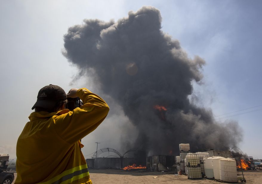 A photographer takes photos as flames and smoke rise from chemical storage tanks near a strawberry farm in Camarillo, Calif., Thursday, May 2, 2013. (AP Photo/Ringo H.W. Chiu)