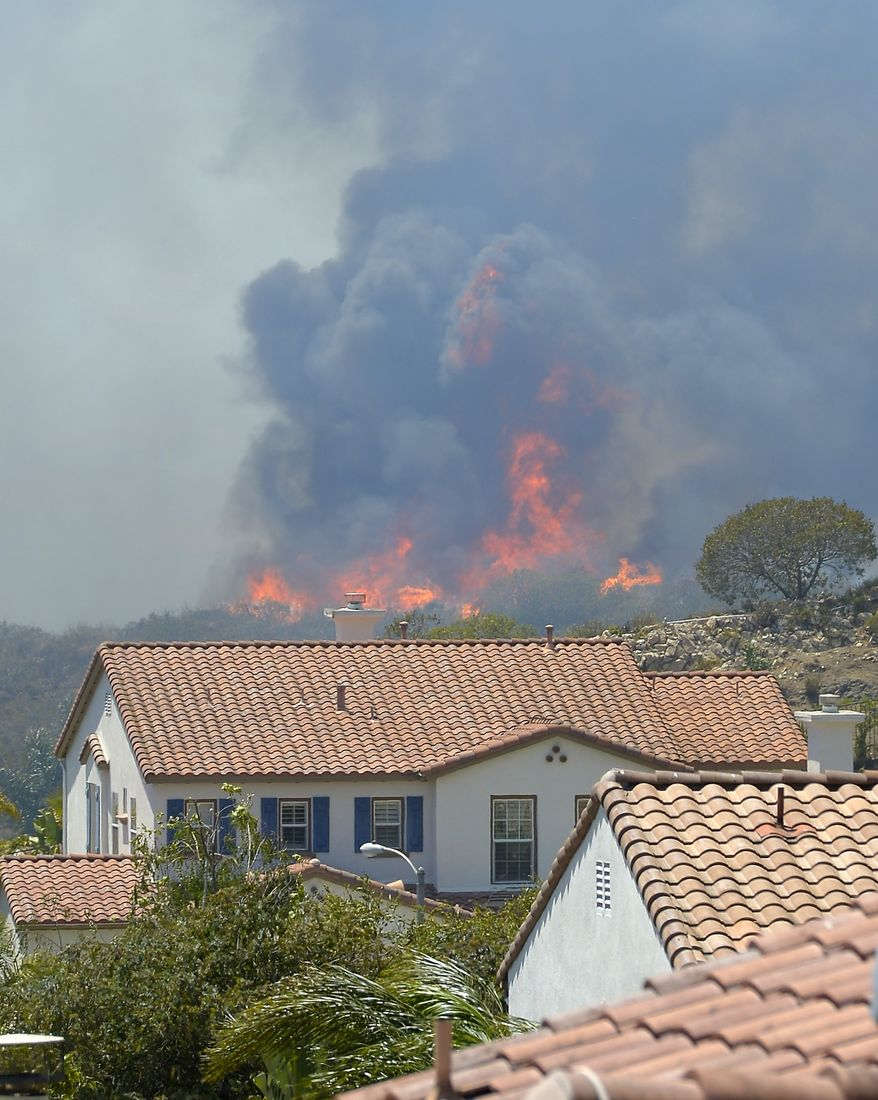Fire burns behind homes during a wildfire that burned several thousand acres, Thursday, May 2, 2013, in Thousand Oaks, Calif.   (AP Photo/Mark J. Terrill)