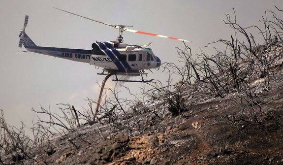 A Kern County Fire helicopter makes a water drop on a hotspot over a hill near Thousand Oaks, Calif. on Thursday, May 2, 2013. Authorities have ordered evacuations of a neighborhood and a university about 50 miles west of Los Angeles where a wildfire is raging close to subdivisions. The blaze on the fringes of Camarillo and Thousand Oaks broke out Thursday morning and was quickly spread by gusty Santa Ana winds. Evacuation orders include California State University, Channel Islands. (AP Photo/Nick Ut)