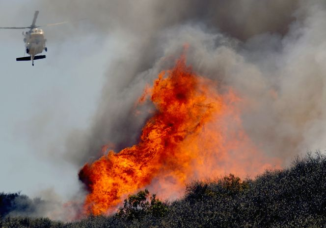 A helicopter makes a water drop on a hotspot over a hill near Thousand Oaks, Calif. on Thursday, May 2, 2013. Authorities have ordered evacuations of a neighborhood and a university about 50 miles west of Los Angeles where a wildfire is raging close to subdivisions. The blaze o