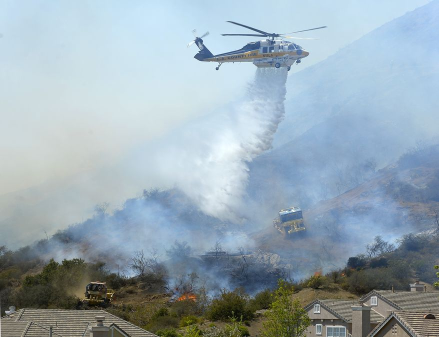 A helicopter makes a water drop on flames as earth movers clear brush along a hillside in Thousand Oaks, Calif., Thursday, May 2, 2013. A Ventura County Fire Department spokeswoman said the wildfire that broke out Thursday morning near Camarillo and Thousand Oaks, 50 miles west of Los Angeles, had spread to over 6,500 acres — more than 10 square miles - forcing evacuations of nearby neighborhoods. (AP Photo/Mark J. Terrill)