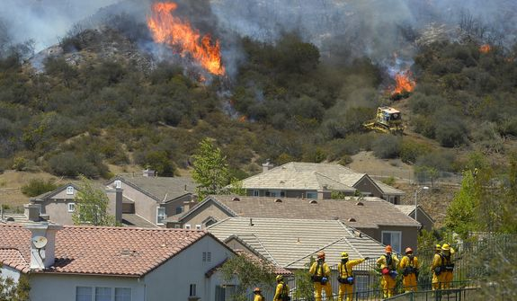 Firefighters stand watch as bulldozers clear a firebreak near a wildfire burning along a hillside near homes in Thousand Oaks, Calif., Thursday, May 2, 2013. A Ventura County Fire Department spokeswoman said the blaze that broke out Thursday morning near Camarillo and Thousand Oaks, 50 miles west of Los Angeles, had spread to over 6,500 acres, forcing evacuations of nearby neighborhoods. (AP Photo/Mark J. Terrill)