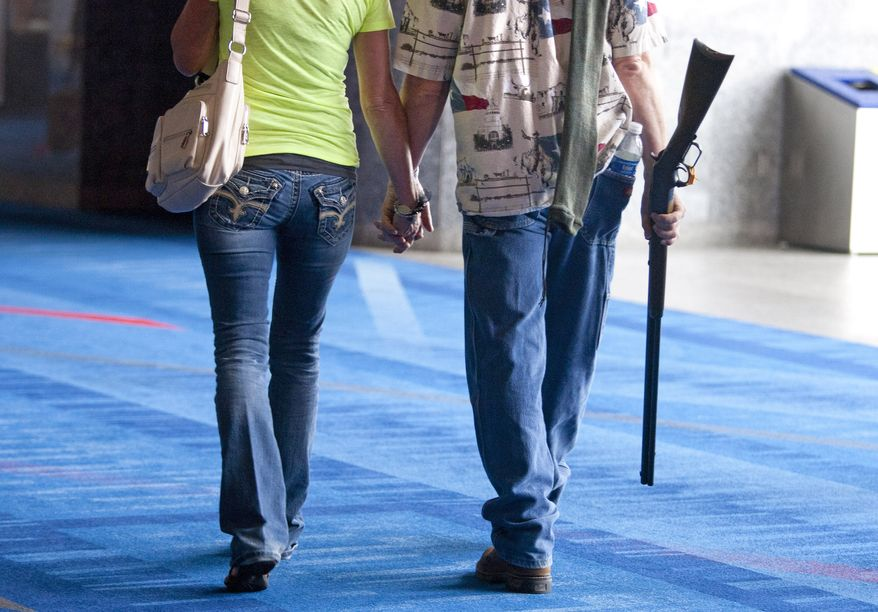Barry Bailey and his wife, Judy, of DeRidder, La., leave after having their 1873 Winchester rifle appraised at the National Rifle Association's Antiques Guns and Gold Showcase on May 2, 2013, during the NRA's 142 Annual Meetings and Exhibits at the George R. Brown Convention Center in Houston. (Associated Press/Houston Chronicle)