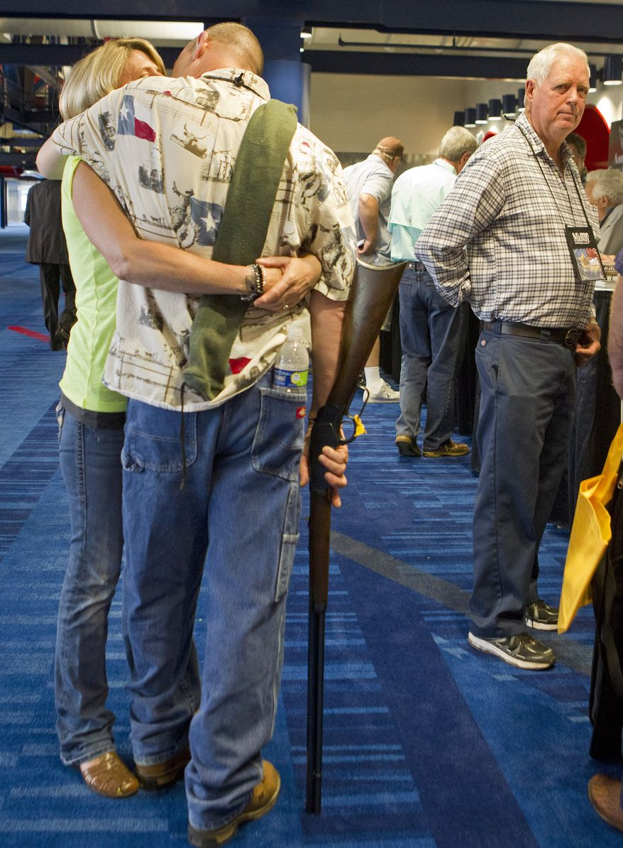 Barry Bailey, of DeRidder, La., gives his wife Judy a kiss, before having their 1873 Winchester rifle appraised at the National Rifle Association's Antiques Guns and Gold Showcase on May 2, 2013, during the NRA's 142 Annual Meetings and Exhibits at the George R. Brown Convention Center in Houston. (Associated Press/Houston Chronicle)