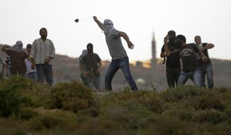 Palestinians hurl stones during clashes with Jewish settlers, not seen, near the West Bank village of Deir Jarir near Ramallah, Friday, May 3, 2013. Tensions are high in the West Bank, captured by Israel in the 1967 Mideast war and claimed by Palestinians as part of their future state. (AP Photo/Majdi Mohammed)