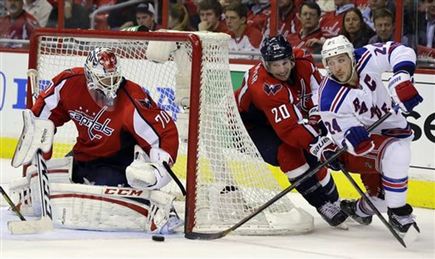 New York Rangers right wing Ryan Callahan (24) shoots as the guarded by Washington Capitals right wing Troy Brouwer (20) and goalie Braden Holtby (70) blocks the shot in the third period of Game 1 of a Stanley Cup NHL playoff hockey series on Thursday, May 2, 2013, in Washington. The Capitals won 3-1. (AP Photo/Alex Brandon)