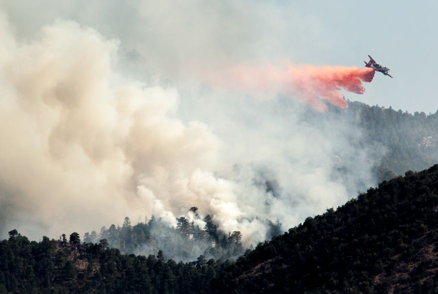 An airplane drops slurry on the Piedra Fire in the Sandia Mountains between Albuquerque and Pacaitas, NM on Thursday, May 2, 2013.  A wildfire is burning in the Sandia Mountains just north of Albuquerque. Firefighters battled the blaze on the ground and from the air, with helicopters and planes dropping water and fire retardant on the flames. (AP Photo/Craig Fritz)