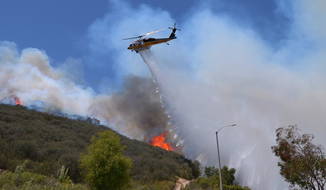 A helicopter makes a water drop on flames as a wildfire burns along a hillside in Thousand Oaks, Calif., Thursday, May 2, 2013. A Ventura County Fire Department spokeswoman said the blaze that broke out Thursday morning near Camarillo and Thousand Oaks, 50 miles west of Los Angeles, had spread to over 6,500 acres, forcing evacuations of nearby neighborhoods. (AP Photo/Mark J. Terrill)