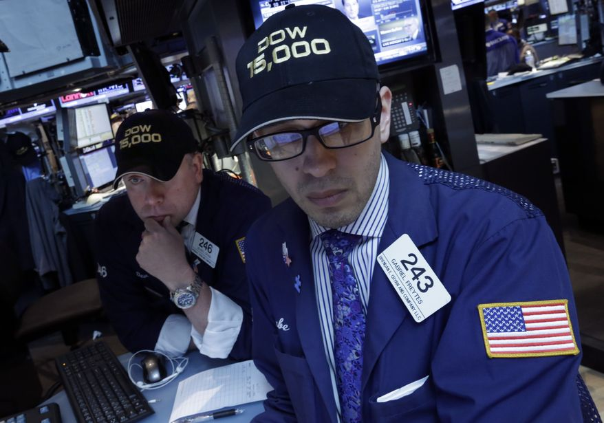 """Specialists Devin Cryan (left) and Gabriel Freytes wear a """"Dow 15,000"""" hats as they work at a post on the floor of the New York Stock Exchange on May 3, 2013. A big gain in the job market lifted the stock market to a record high. The Dow Jones industrial average crossed 15,000 for the first time, and the Standard and Poor's 500 index, a broader market measure, rose above 1,600. (Associated Press)"""