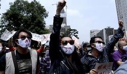 """Chinese people wear face masks with """"No to Kunming PX,"""" paraxylene, written, chant slogans as they hold protest against a planned refinery project in downtown Kunming in southwest China's Yunnan province Saturday, May 4, 2013. (Associated Press)"""
