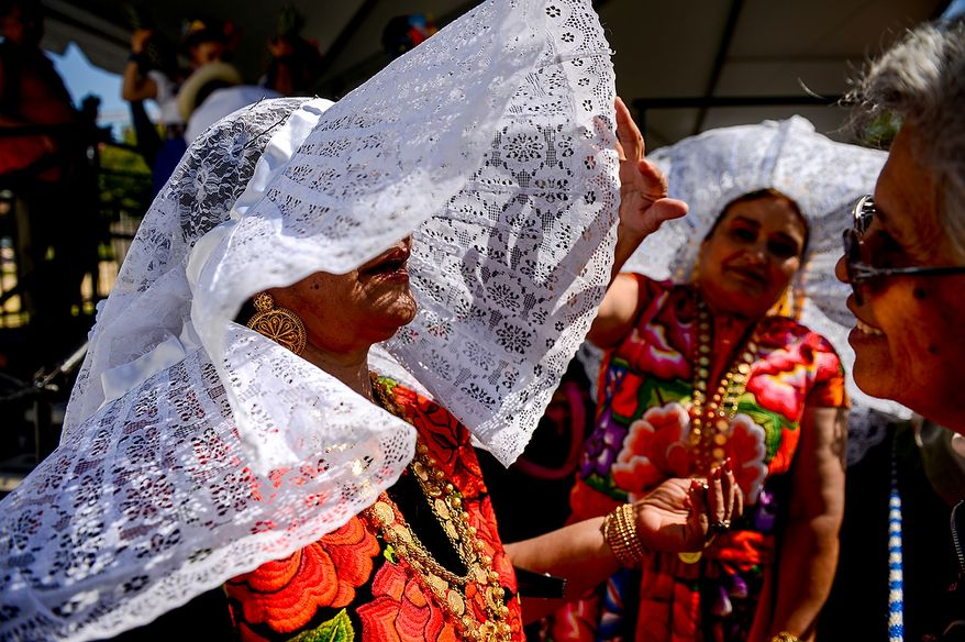 Sisters Emma Gonzalez (second from left) and Martha Montero (left), originally from Wahaca, Mexico, wear traditional tehuanas clothing at the annual Cinco de Mayo celebration on the National Mall in Washington on Sunday, May 5, 2013. (Andrew Harnik/The Washington Times)