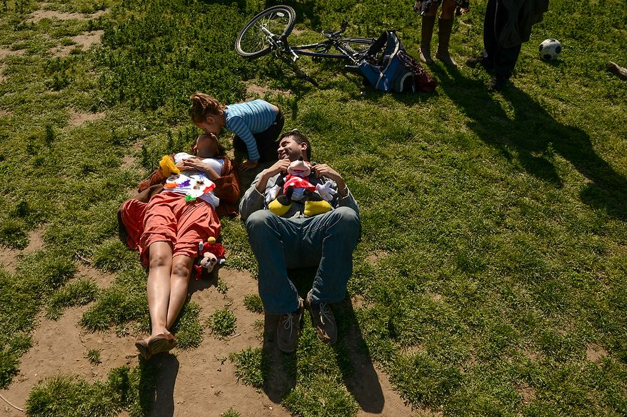 A woman gets a kiss from her daughter as she relaxes with her boyfriend at the annual Cinco de Mayo celebration on the National Mall in Washington on Sunday, May 5, 2013. (Andrew Harnik/The Washington Times)