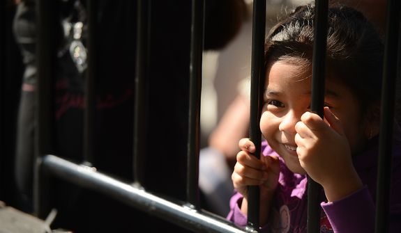 A young girl watches performances onstage at the annual Cinco de Mayo celebration on the National Mall in Washington on Sunday, May 5, 2013. (Andrew Harnik/The Washington Times)