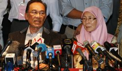Malaysian opposition leader Anwar Ibrahim (left) and his wife, Wan Azizah, speak during a press conference at a hotel in Kuala Lumpur on Monday, May 6, 2013. Malaysia's governing coalition fended off a tough election challenge to extend its 56-year rule. (AP Photo/Vincent Thian)