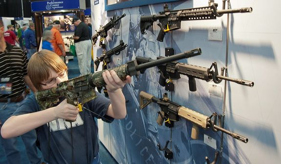 A young man who chose not to give his name sizes-up an assault style rifle during the National Rifle Association's annual convention Friday, May 3, 2013 in Houston. (AP Photo/Steve Ueckert)