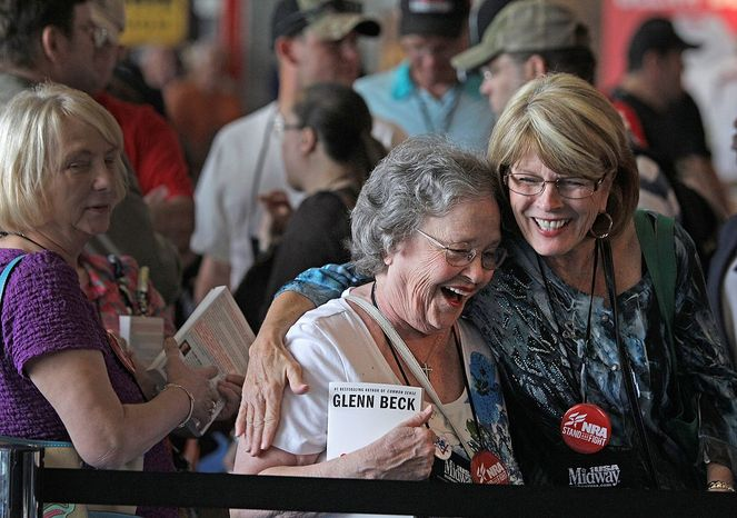 Eby Owen, center, of Dunedin, Fla., and Debbie Brinson, right, of San Antonio share a hug as they wait in line for the Glenn Beck book signing event during the NRA convention at the George R. Brown Convention Center  Saturday, May 4, 2013, in Houston. National Rifle Association leaders told members Saturday that the fight against gun control legislation is far from over, with battles yet to come in Congress and next year's midterm elections, but they vowed that none in the organization will ever have to surrender their weapons. (AP Photo/Houston Chronicle,  Melissa Phillip)