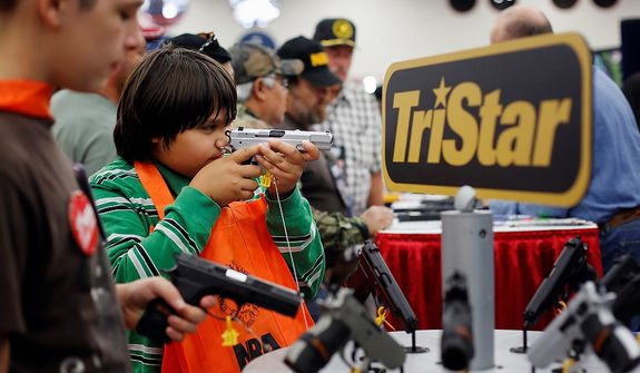 Brothers, 10-year-old Kayden La, center. and 13-year-old Jacob La, left, inspect pistols at a booth, during the NRA Annual Meeting of Members at the National Rifle Association's 142 Annual Meetings and Exhibits in the George R. Brown Convention Center Saturday, May 4, 2013, in Houston. National Rifle Association leaders told members Saturday that the fight against gun control legislation is far from over, with battles yet to come in Congress and next year's midterm elections, but they vowed that none in the organization will ever have to surrender their weapons. (AP Photo/Houston Chronicle, Todd Spoth)