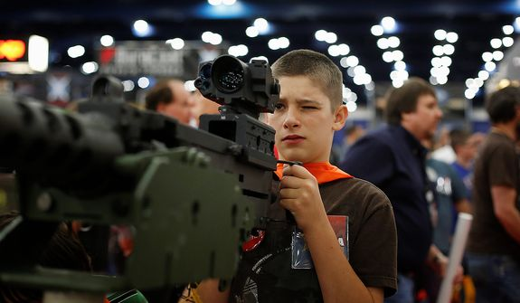 13-year-old Jacob La looks down the sight of a mounted machine gun, during the NRA Annual Meeting of Members at the National Rifle Association's 142 Annual Meetings and Exhibits in the George R. Brown Convention Center Saturday, May 4, 2013, in Houston. National Rifle Association leaders told members Saturday that the fight against gun control legislation is far from over, with battles yet to come in Congress and next year's midterm elections, but they vowed that none in the organization will ever have to surrender their weapons. (AP Photo/Houston Chronicle, Todd Spoth)