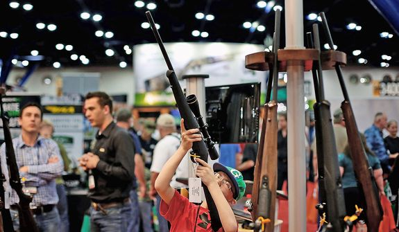 11-year-old Ryan Weaver inspects a rifle, during the NRA Annual Meeting of Members at the National Rifle Association's 142 Annual Meetings and Exhibits in the George R. Brown Convention Center Saturday, May 4, 2013, in Houston. National Rifle Association leaders told members Saturday that the fight against gun control legislation is far from over, with battles yet to come in Congress and next year's midterm elections, but they vowed that none in the organization will ever have to surrender their weapons. (AP Photo/Houston Chronicle, Todd Spoth)