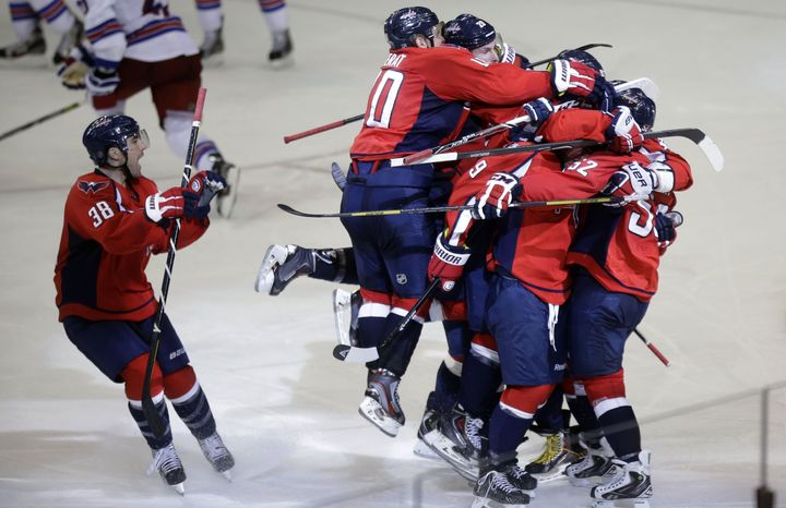Washington Capitals defenseman Mike Green, right, is congratulated by teammates after he scored the game winning goal in overtime of Game 2 of a Stanley Cup NHL playoff hockey series against the New York Rangers on Saturday, May 4, 2013, in Washington. The Capitals defeated the Rangers 1-0 in overtime. (AP Photo/Evan Vucci)