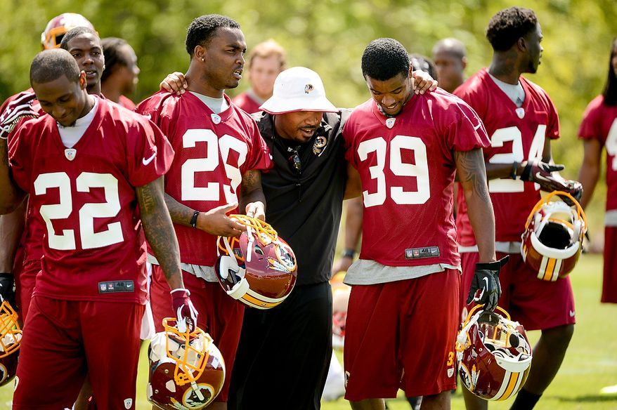 Newly drafted Washington Redskins safety Bacarri Rambo (second from left) and cornerback David Amerson (39)  come off the field with a coach following rookie minicamp at Redskins Park in Ashburn, Va., on Sunday, May 5, 2013. Also pictured is tryout cornerback Akeem Auguste (22). (Andrew Harnik/The Washington Times)