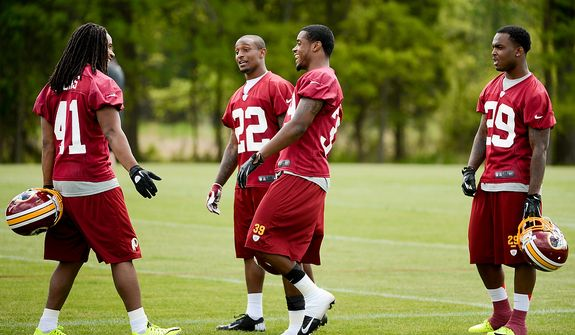 Newly drafted Washington Redskins safety Phillip Thomas (left), cornerback David Amerson (second from right) and safety Bacarri Rambo (right) talk together on the sidelines during the Washington Redskins' rookie minicamp at Redskins Park, Ashburn, Va., Sunday, May 5, 2013. Also pictured is tryout cornerback Akeem Auguste (22). (Andrew Harnik/The Washington Times)