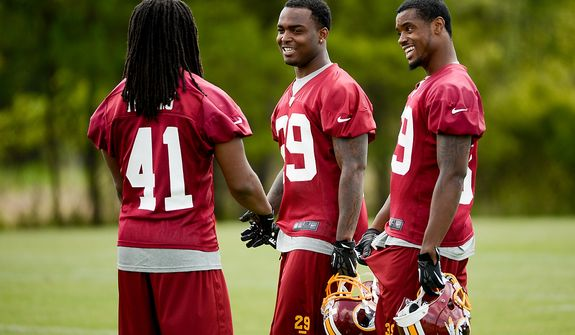 Newly drafted Washington Redskins safety (from left) Phillip Thomas (41), safety Bacarri Rambo (29) and cornerback David Amerson (39) talk together on the sidelines during the team's rookie minicamp at Redskins Park in Ashburn, Va., on Sunday, May 5, 2013. (Andrew Harnik/The Washington Times)