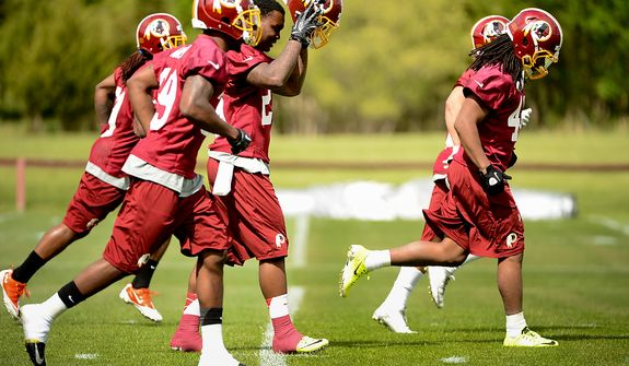 Newly drafted Washington Redskins safety Bacarri Rambo (29) puts on his helmet during the Washington Redskins' rookie minicamp at Redskins Park, Ashburn, Va., Sunday, May 5, 2013. (Andrew Harnik/The Washington Times)