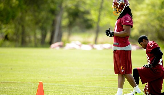 Newly drafted Washington Redskinis safety Phillip Thomas (second from right) watches scrimmage drills from the sidelines at the team's rookie minicamp at Redskins Park in Ashburn, Va., on Sunday, May 5, 2013. (Andrew Harnik/The Washington Times)