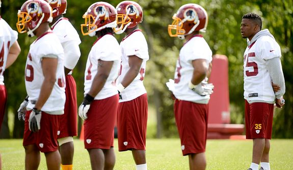 Newly drafted Washington Redskins running back Chris Thompson (right) watches drills at the team's rookie minicamp at Redskins Park in Ashburn, Va., on Sunday, May 5, 2013. Thompson is recovering from a torn ACL in his left knee. (Andrew Harnik/The Washington Times)