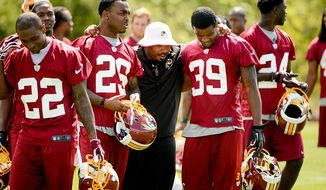Newly drafted Washington Redskins safety Bacarri Rambo (second from left) and cornerback David Amerson (right) come off the field with a coach following minicamp at Redskins Park in Ashburn, Va., on Sunday, May 5, 2013. Also pictured is tryout cornerback Akeem Auguste (22). (Andrew Harnik/The Washington Times)