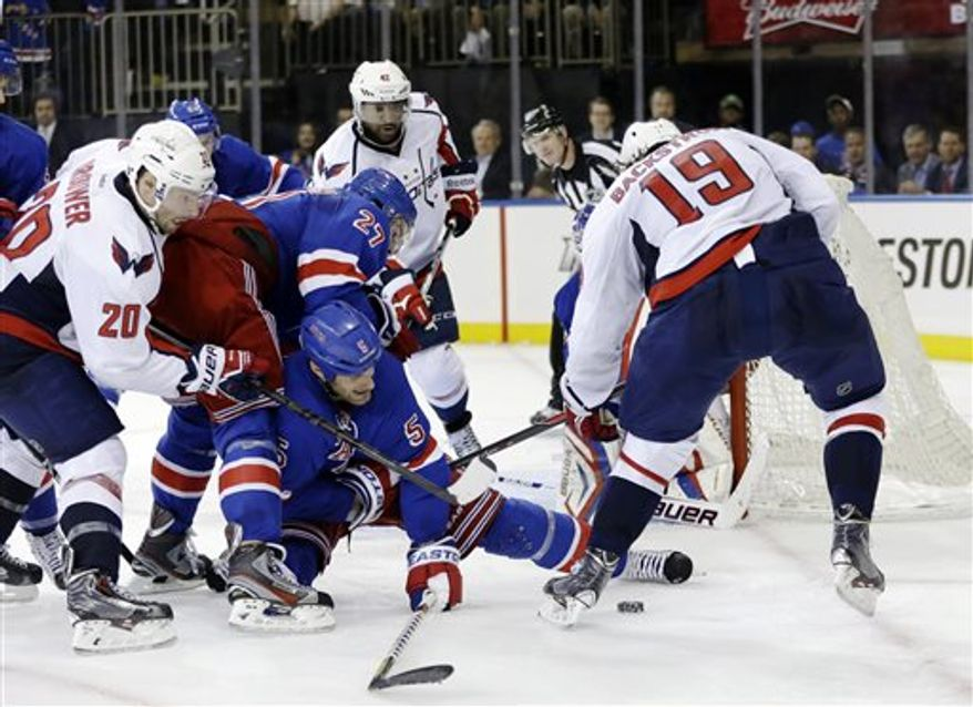 New York Rangers defensemen Ryan McDonagh (27) and Dan Girardi (5) fend off Washington Capitals right wing Troy Brouwer (20) and center Nicklas Backstrom (19), of Sweden, on a power play late in the third period of Game 3 of their first-round NHL hockey Stanley Cup playoff series in New York, Monday, May 6, 2013. The Rangers won 4-3. (AP Photo/Kathy Willens)