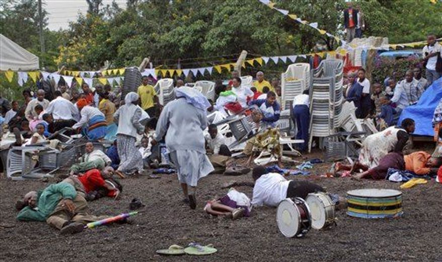 Wounded churchgoers lie on the ground as Roman Catholic nuns run for cover after a blast at the St. Joseph Mfanyakazi Roman Catholic Church in Arusha, Tanzania Sunday, May 5, 2013. A Tanzanian police official says a woman died and over 40 people were seriously injured when a bomb exploded in the Roman Catholic Church in northern Tanzania, with eyewitnesses reporting that the bomb was thrown from a motorcycle. (Associated Press)