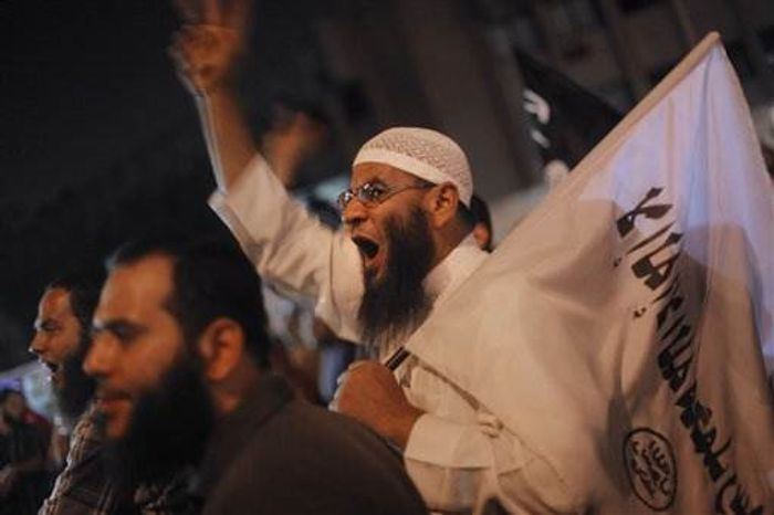 """Egyptians shout slogans in front of the state security headquarters in Cairo, Egypt, late Thursday, May 2, 2013. Arabic on the flag reads, """"no God but Allah and Muhammad is his messenger."""" (Associated Press)"""