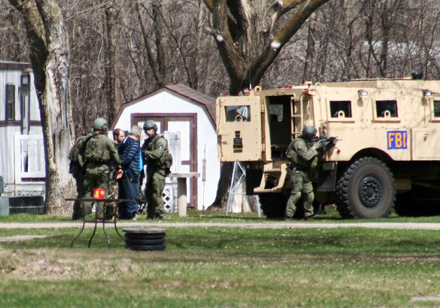 FBI agents are pictured with Buford Rogers (back left) and an unidentified man during a raid on a mobile home in Montevideo, Minn. Authorities said Monday that Mr. Rogers had been arrested and that the FBI believes authorities had disrupted a potential terror attack after a search of the home turned up Molotov cocktails, suspected pipe bombs and firearms. (AP Photo/Montevideo American-News, Jeremy Jones)