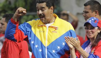 ** FILE ** Venezuela's President Nicolas Maduro holds his fist to supporters as his companion Cilia Flores applauds during a pro-government May Day march in Caracas, Venezuela, Wednesday, May 1, 2013. (AP Photo/Ariana Cubillos)