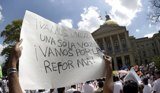 A protester for immigration reform holds a sign during a rally at the Georgia Capitol in Atlanta on April 10, 2013. (Associated Press) **FILE**