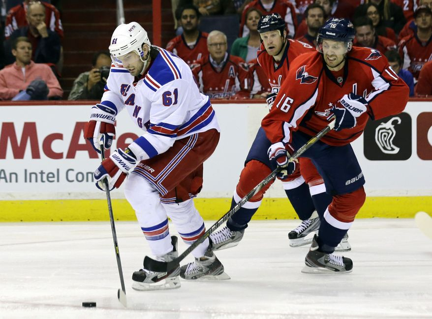 New York Rangers left wing Rick Nash (61) looks to pass as he guarded by Washington Capitals right wing Eric Fehr (16) in the first period of Game 1 of a Stanley Cup NHL playoff hockey series on Thursday, May 2, 2013, in Washington. (AP Photo/Alex Brandon)