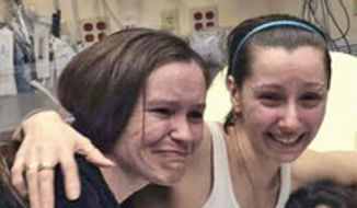 Amanda Berry (right) is reunited with her sister Beth Serrano in a Cleveland hospital Monday after she was reported missing a decade ago. (Berry Family handout via Associated Press)