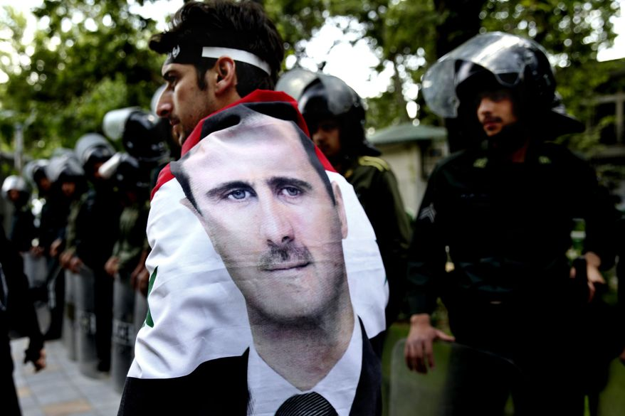 An Syrian man wrapped in a Syrian flag with a portrait of President Bashar Assad, walks past anti riot police during an anti-Israeli demonstration in front of the U.N. office in Tehran, Iran, Monday, May 6, 2013. (AP Photo/Ebrahim Noroozi)