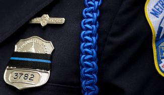 Officers cover their badges with a black stripe for Blue Mass at St. Patrick Catholic Church, Washington, D.C., Tuesday, May 7, 2013. The Blue Mass is held to pray for those in law enforcement and fire safety, remember those who have fallen, and support those who serve at the beginning of National Police Week.  (Andrew Harnik/The Washington Times)