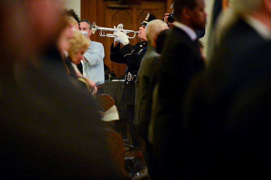 A police officer plays taps for officers who have died in the line of duty in 2012 during Blue Mass at St. Patrick Catholic Church, Washington, D.C., Tuesday, May 7, 2013. The Blue Mass is held to pray for those in law enforcement and fire safety, remember those who have fallen, and support those who serve at the beginning of National Police Week.  (Andrew Harnik/The Washington Times)