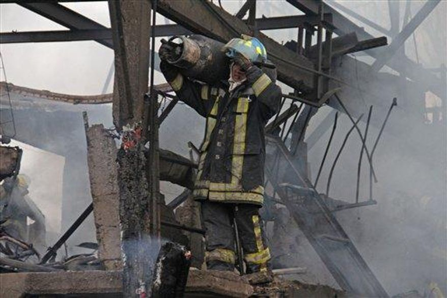 A firefighter carries a gas tank away from a destroyed home after a gas tanker truck exploded on a nearby highway in the Mexico City suburb of Ecatepec early Tuesday, May 7, 2013. The blast killed and injured dozens, according to the Citizen Safety Department of Mexico State. (AP Photo/Gabriela Sanchez)