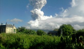 A mushroom of volcanic ash shoots up into the sky from Mount Mayon, one of the Philippines' most active volcanoes, after daybreak as seen from Legazpi city in Albay province, about 285 miles southeast of Manila, on Tuesday, May 7, 2013. (AP Photo/Philippine Institute of Volcanology and Seismology)