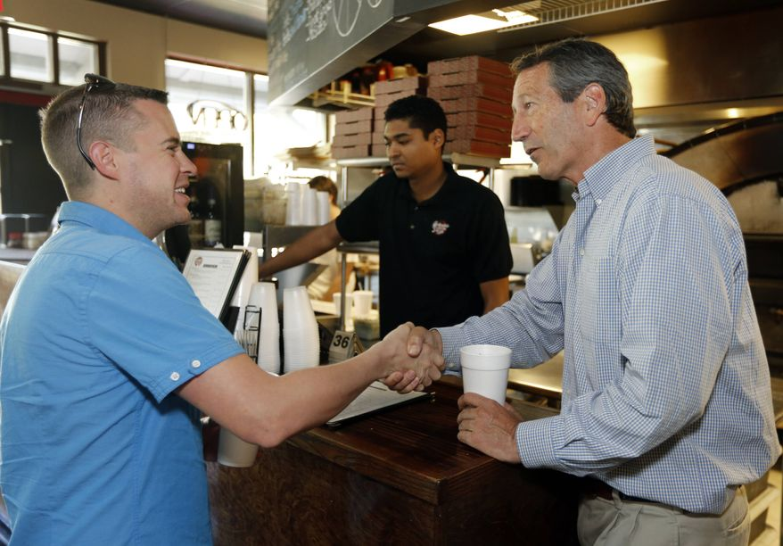 Former South Carolina Gov. Mark Sanford, right, speaks with voter Travis Holt, a mechanic with the U.S. Air Force, at Orlando's Pizza in Daniel Island, S.C., on Monday, May 6, 2013. Server Kevin Caughman works at rear. Sanford is making his last campaign push against his Democratic opponent, Elizabeth Colbert Busch, before Tuesday's special election. (AP Photo/Mic Smith)