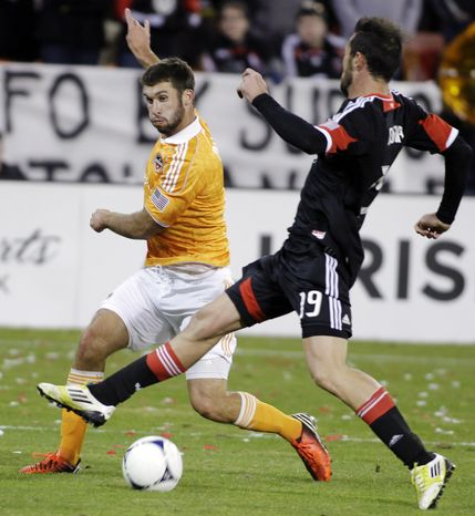 **FILE** Houston Dynamo's Will Bruin, left, kicks the ball as D.C. United's Emiliano Dudar (19) defends during the second half of the second game of an MLS soccer Eastern Conference final playoff series, Sunday, Nov. 18, 2012, in Washington. The Dynamo advanced to their secon